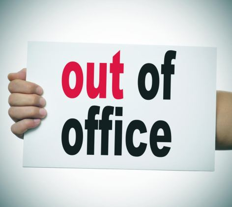 arm holding sign with Out of Office on it