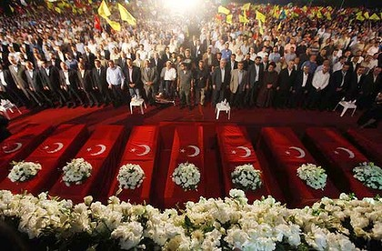 Rallying cry: Hezbollah supporters gather around mock coffins representing those who died on the Mavi Marmara, and a video image shows shrouded bodies on board.