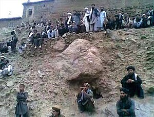 Watching ... this frame grab shows a gathering of people watching the execution by gunfire of a woman married to a member of a hardline Taliban militant group.