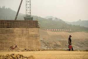 A local worker is dwarfed by the nascent Nam Ou 2 Dam.