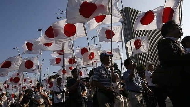 "Members of the nationalist movement ""Ganbare Nippon"" march  with Japanese national flags while paying tribute to the war dead near Yasukuni Shrine."