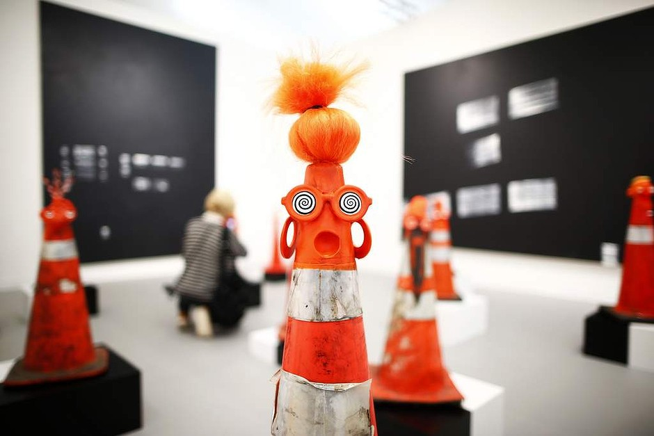 "A visitor photographs part of Robert Pruitt's ""Safety Cones"" at the Gavin Brown's Enterprise from New York's stand at the Frieze Art Fair in central London"