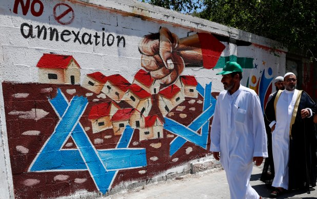 Hamas supporters walk past a sign opposing Israel's annexation plans