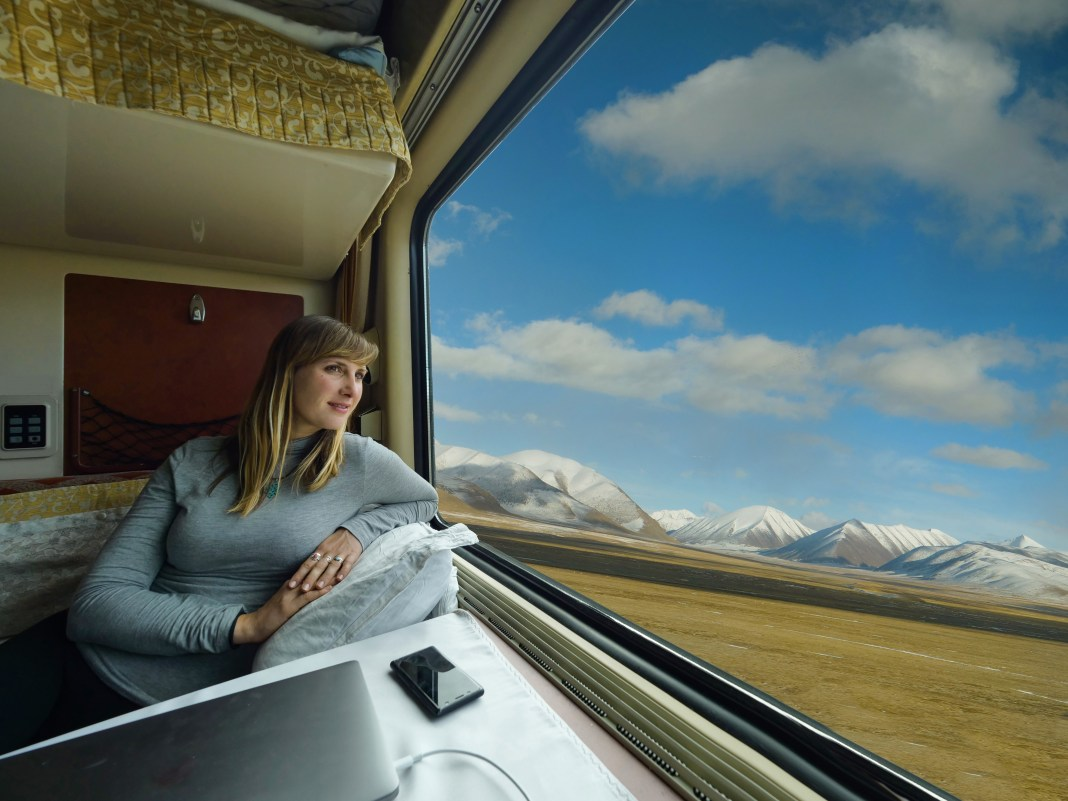 A woman stares out at the Tibetan plains while propped up on a pillow in a sleeper train carriage.