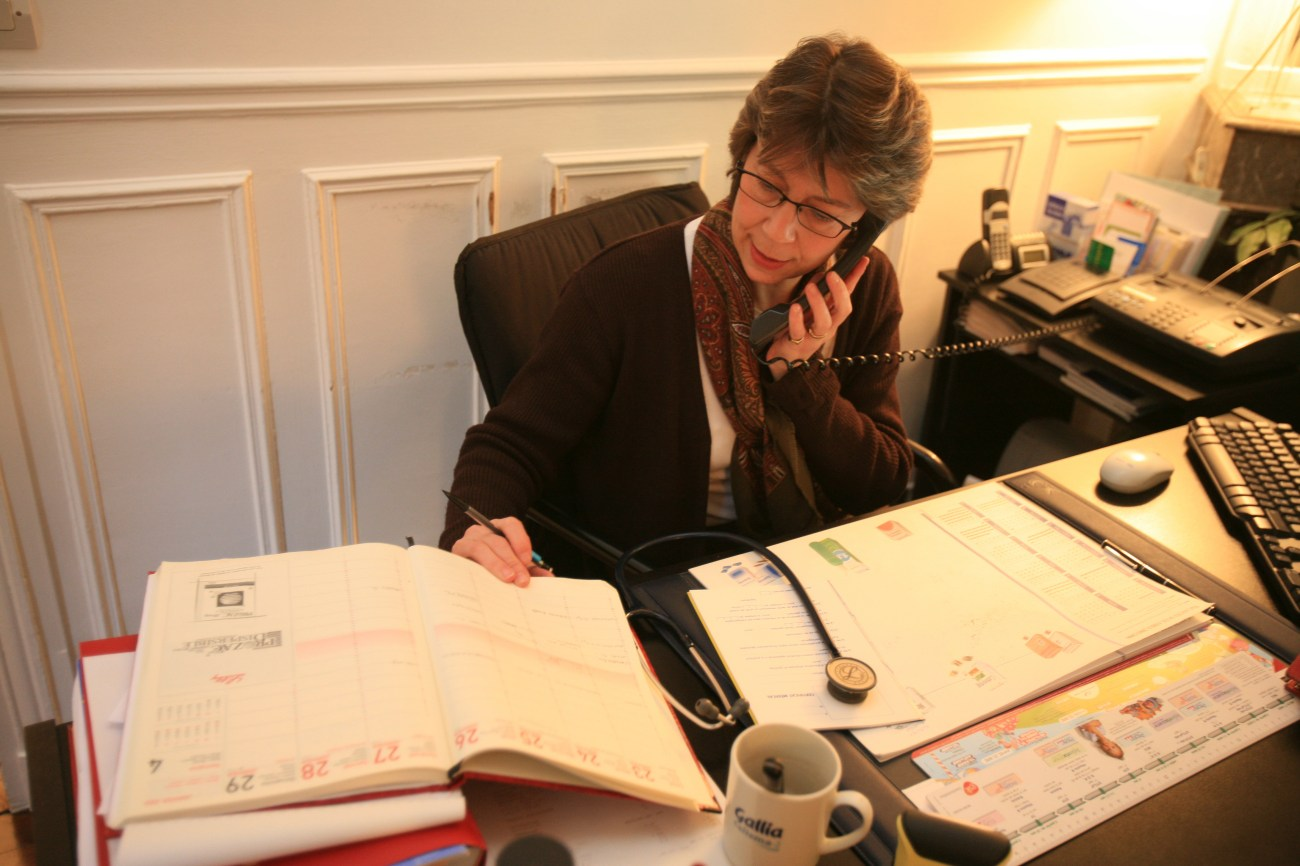 A doctor at her desk on the telephone.
