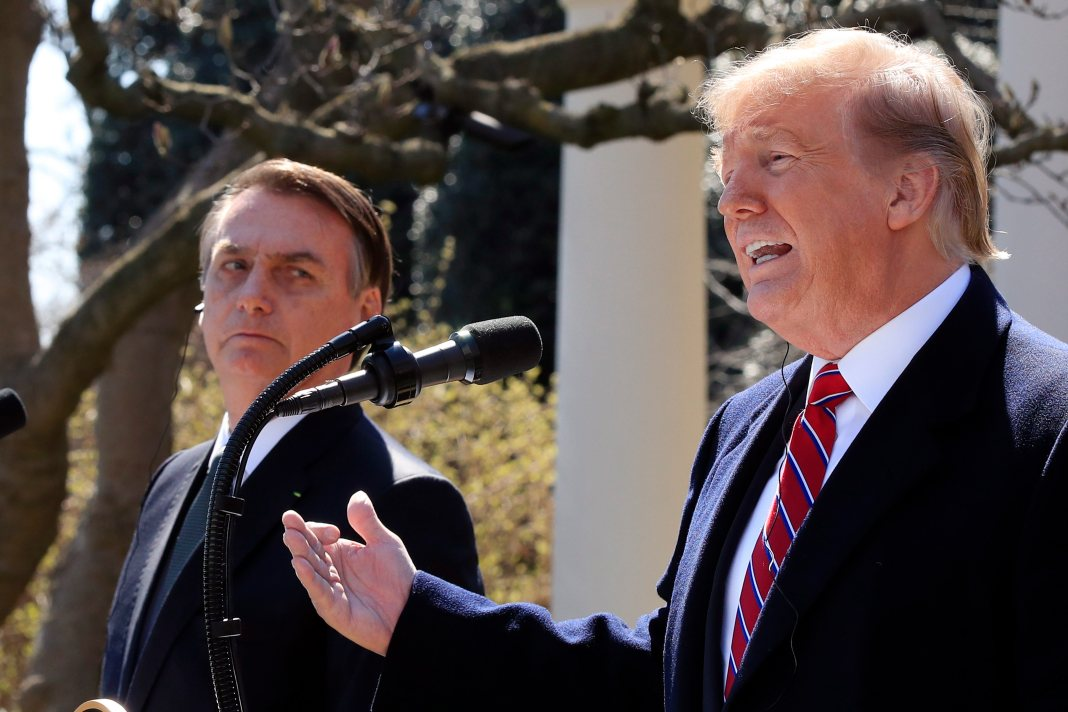 Trump gestures while speaking into a microphone with Bolsonaro looking on.