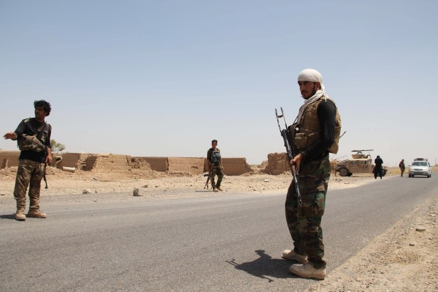 Afghan security officials standing guard on a road.