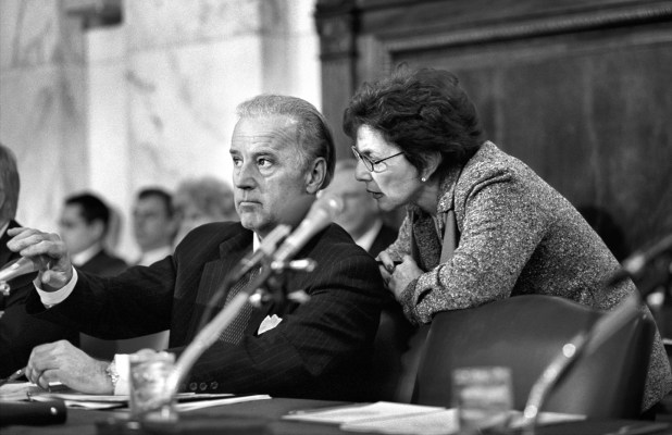 Black and white photo of Barbara Boxer speaking into a seated Joe Biden's ear in the Senate