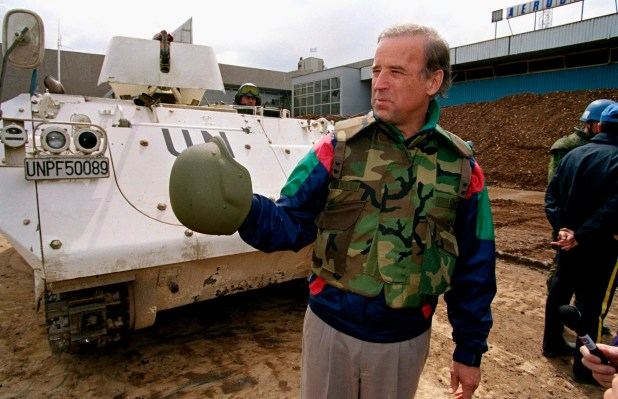 Joe Biden in Bosnia wearing camouflage and standing near a tank