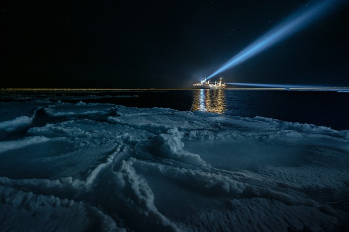 Seen from a sea ice floe, a large ship shines white light into the sky on the horizon.