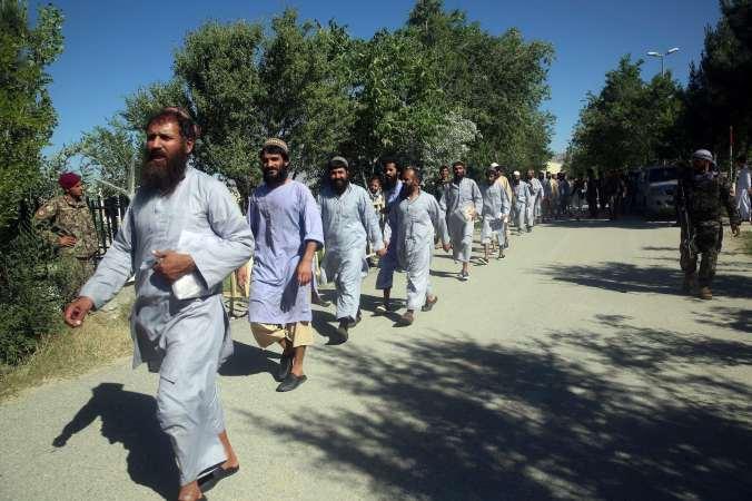 Bearded men walk in a single-file line.