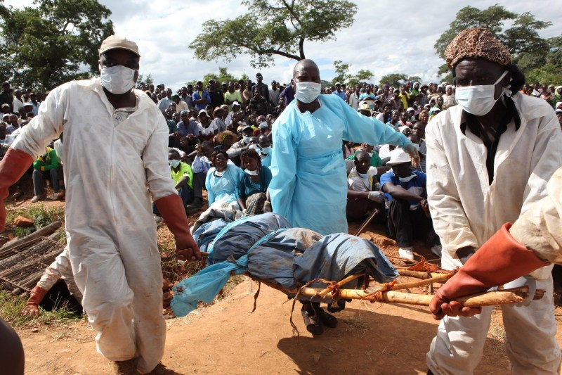 Men in surgical masks carry body on a stretcher.