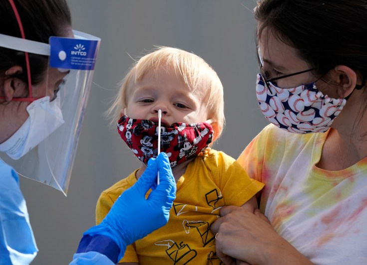A very young child is nasal swabbed for coronavirus by a health professional in a mask and face shield