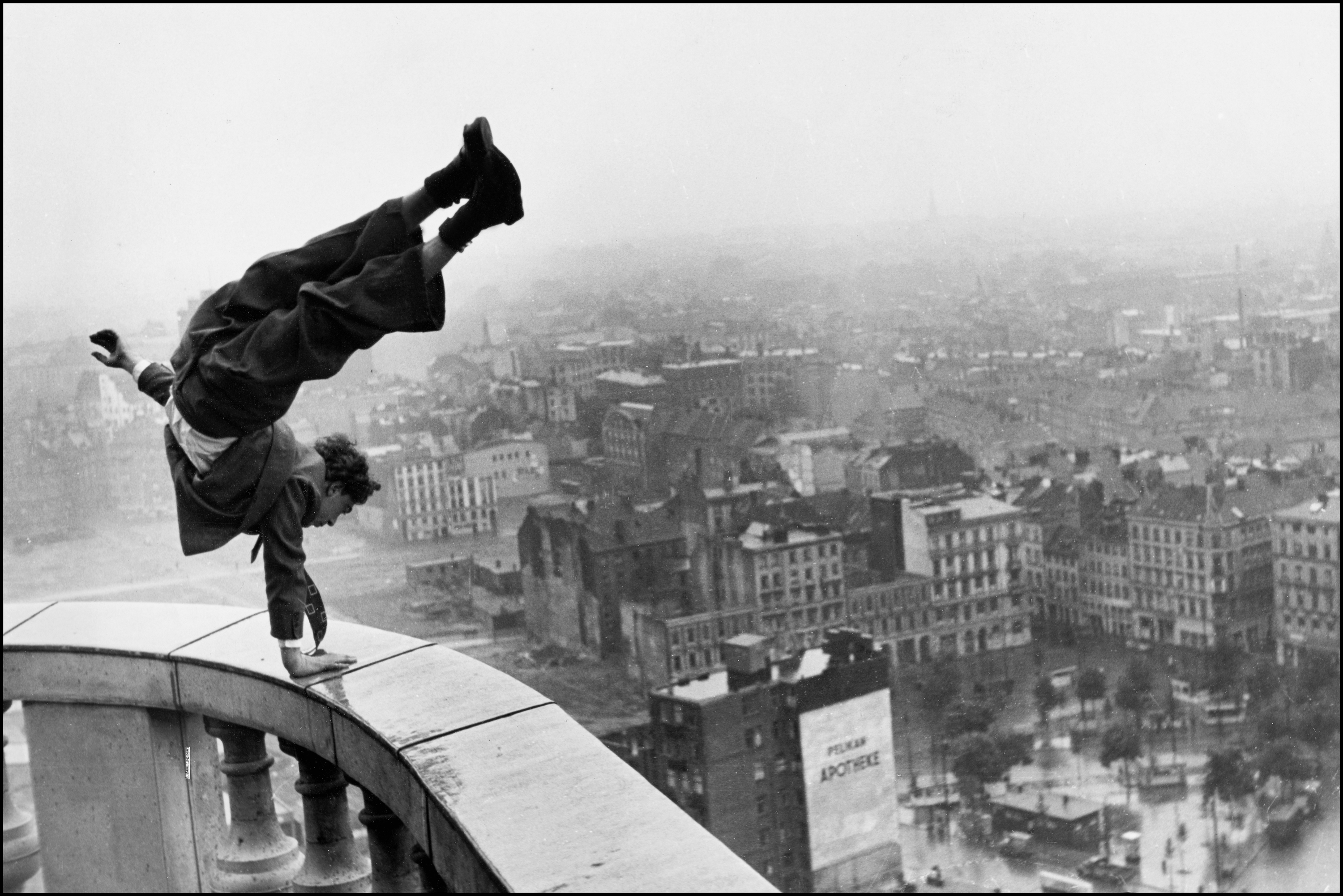 A man in a suit doing a one-armed handstand on a rain-wet balcony railing high above a city, his legs curling over towards the city.