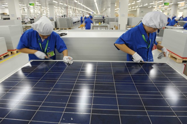 Two workers with white gloves work on a solar panel.