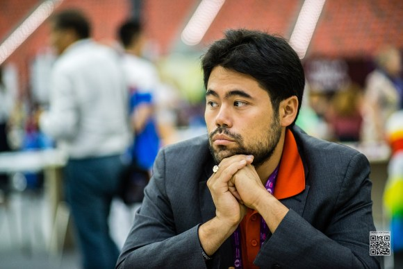 Hikaru Nakamura in a suit at a chess tournament.