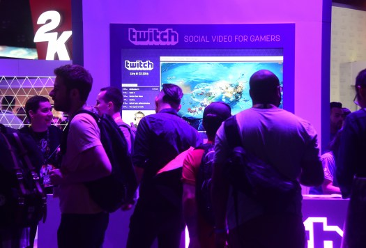 A group of young people standing under purple lights in front of a Twitch booth at a vide game convention.