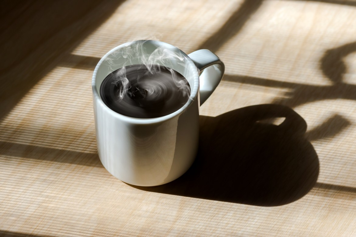 Steaming coffee cup on table.