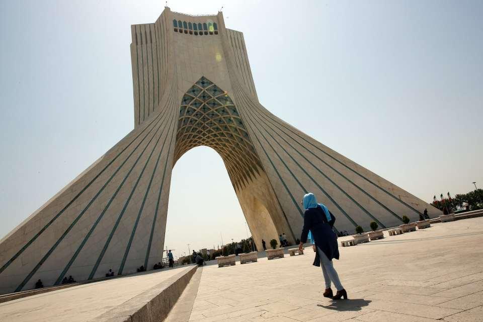 Woman walking towards large archway in Tehran.
