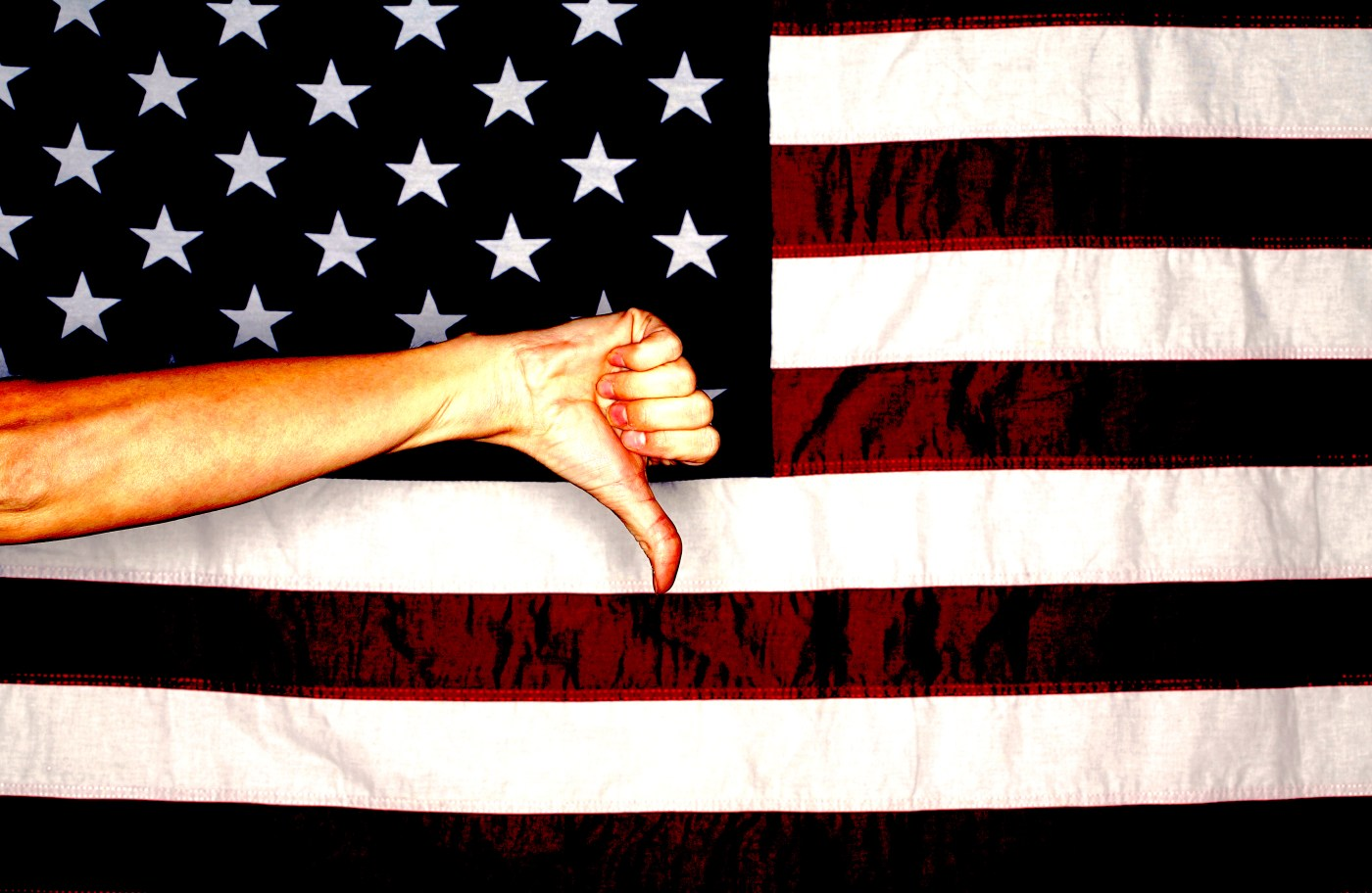American flag with hand making a thumbs down