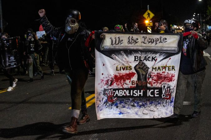 Protesters carry a banner reading 'Black Lives Matter,' 'Abolish ICE,' and 'We the People'