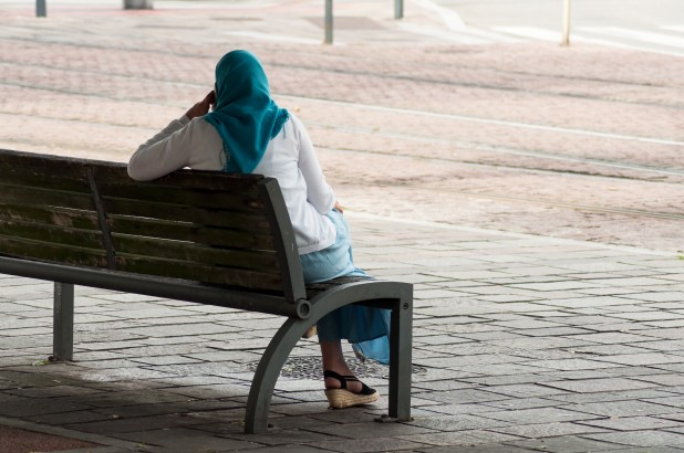 A woman sits on a bench.