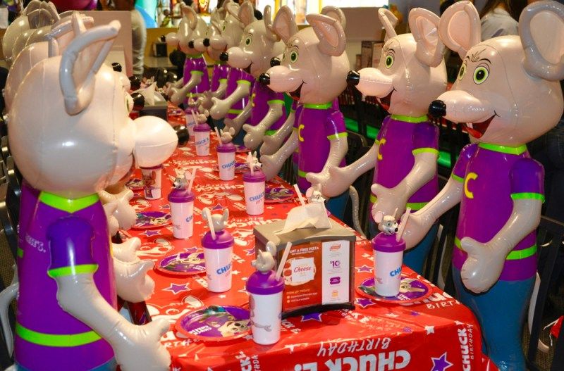 Lots of Chuck E. Cheese mice at a table.