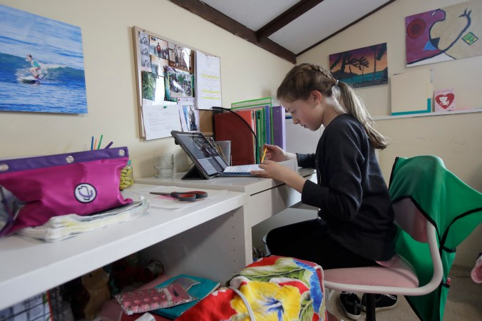 a girl looks over a piece of paper in front of a laptop in a bedroom