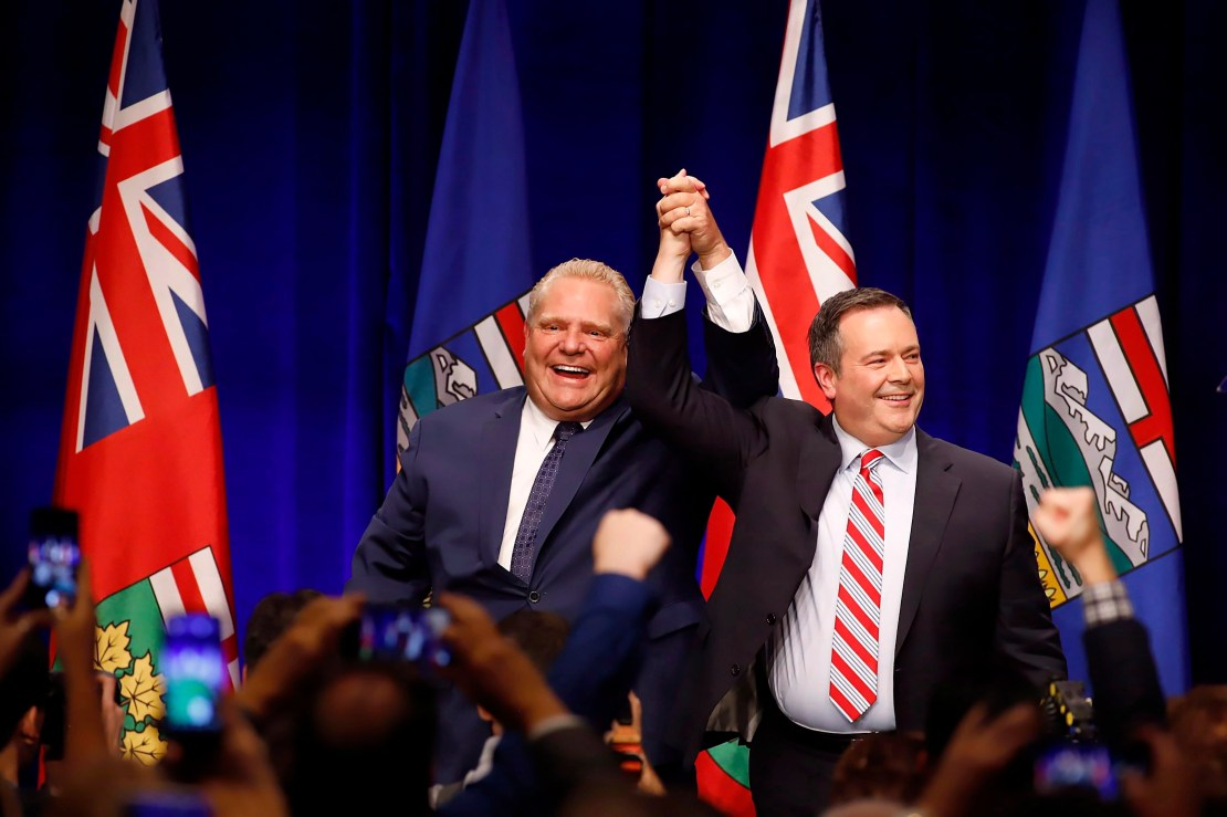 Jason Kenney and Doug Ford clasp raised hands