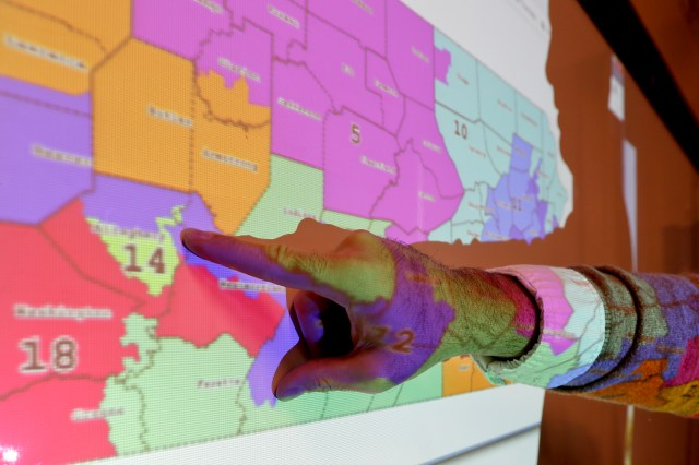 A finger points at a map