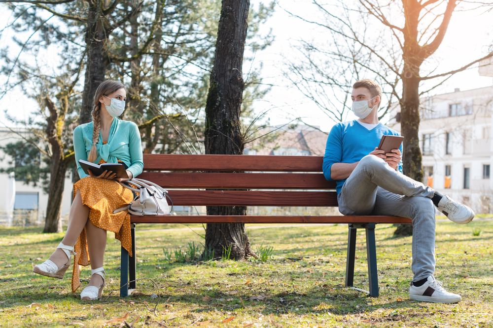 A man and a woman sit apart on a park bench wearing face masks.
