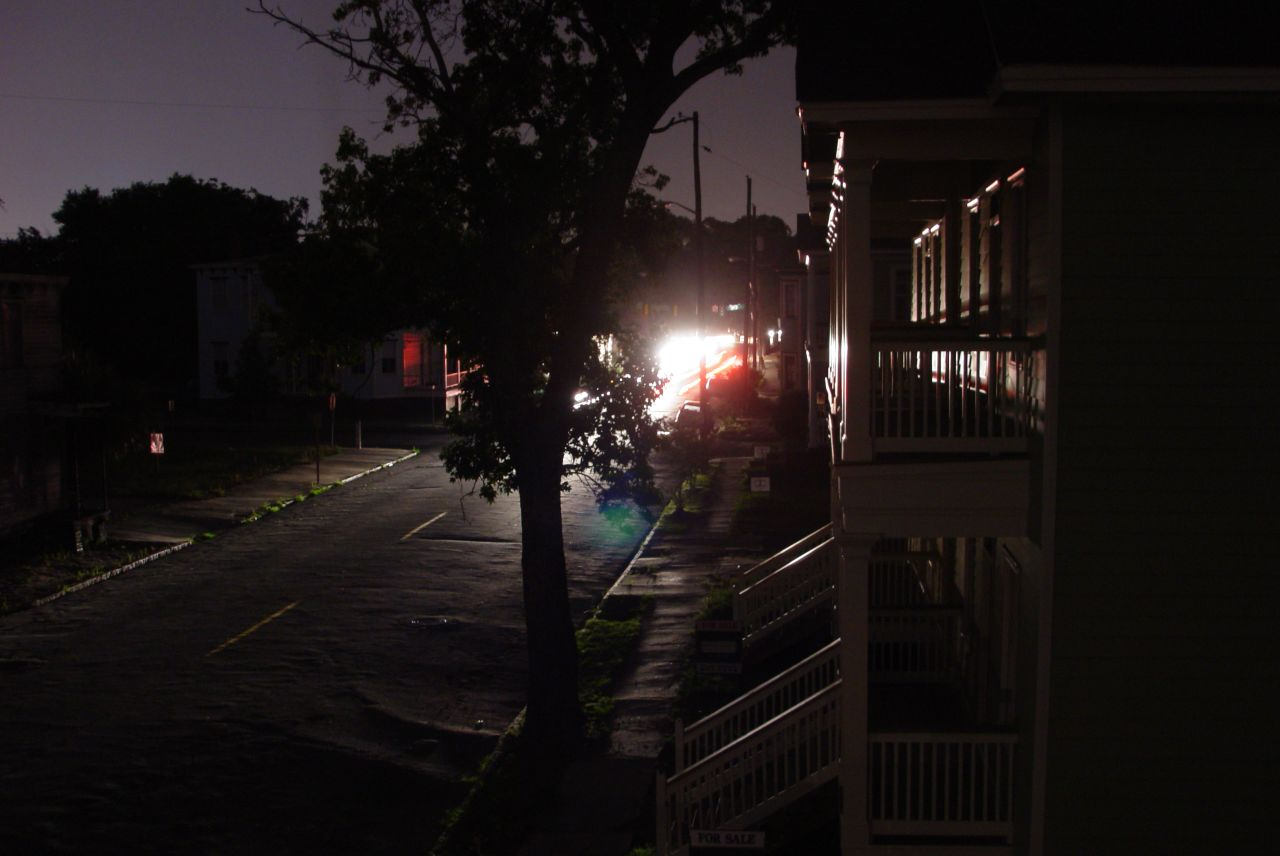 A darkened street with car lights in the distance