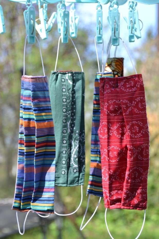 Four cloth masks hanging on a clothesline.