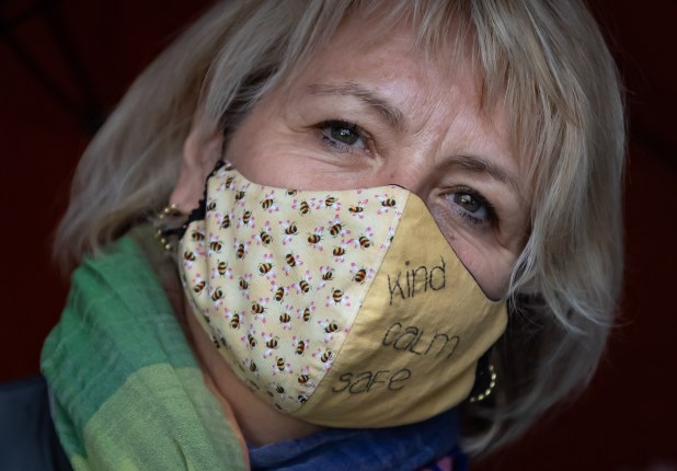 Dr. Bonnie Henry wearing a cloth mask featuring bees and embroidered with the words 'kind calm safe'