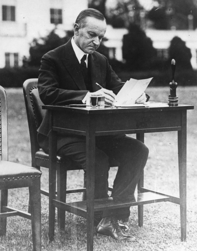 President Calvin Coolidge filling out his absentee ballot at a desk outside of the White House.