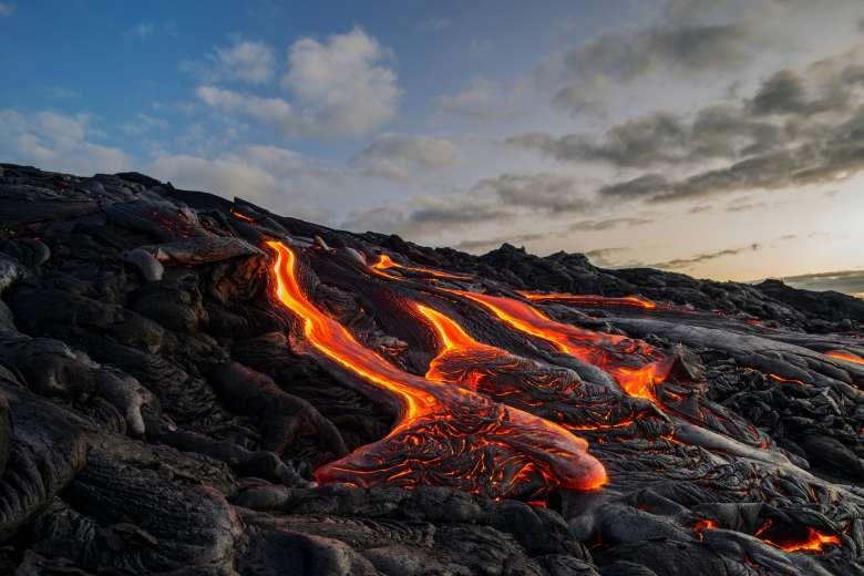 Lava fundida fluyendo por una colina de lava solidificada