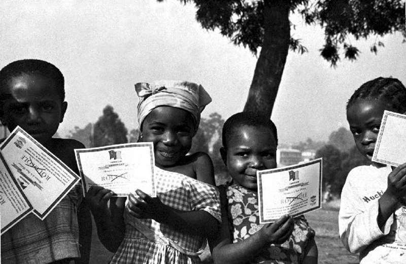 Unos niños muestran certificados de vacunación de la viruela