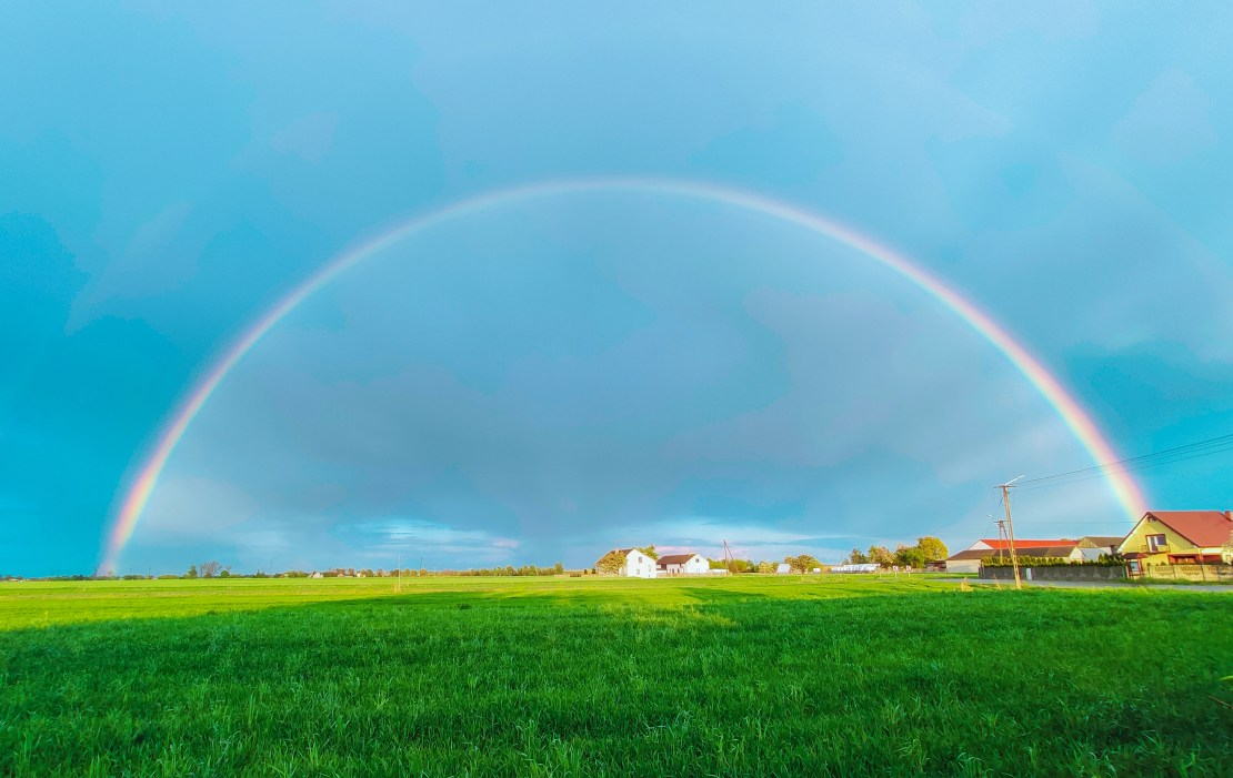 A rainbow over a field against a blue sky.