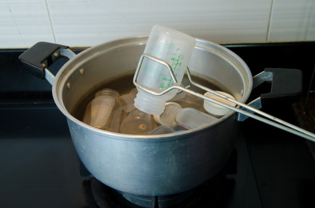 A pair of tongs lifting a plastic baby bottle from a boiling pan.