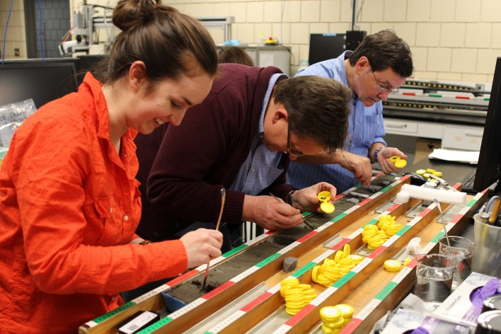 scientists working with a cross-section of a sediment core