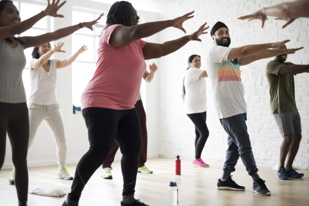 Group of people dancing in a gym.