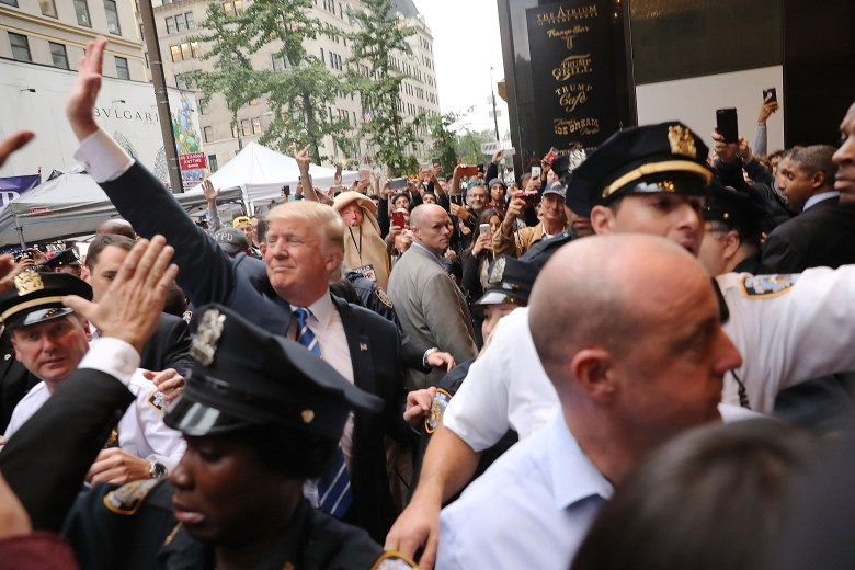 Trump, surrounded by police, waves to supporters in a crowd with protesters in the background