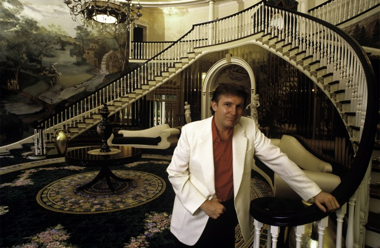 Trump in a high-ceilinged foyer with dramatic wallpaper, rug and staircase