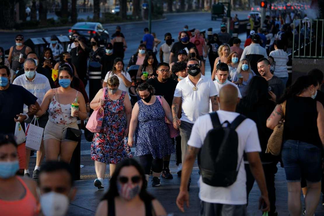 Crowds of people walking on sidewalks in Las Vegas, some wearing masks, some not.