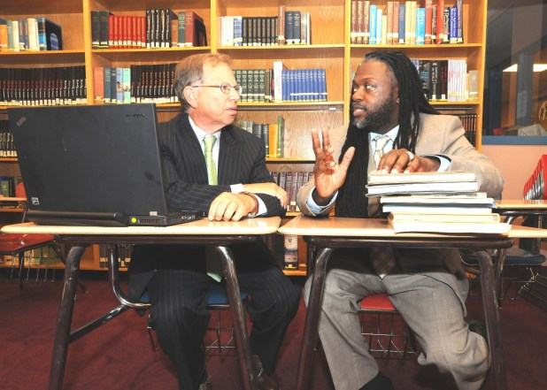 Two founders of the Pathways in Technology Early College High School sit at a table and talk.