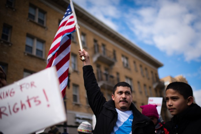 Immigrant man wearing a Guatemalan flag shirtholds an American flag.