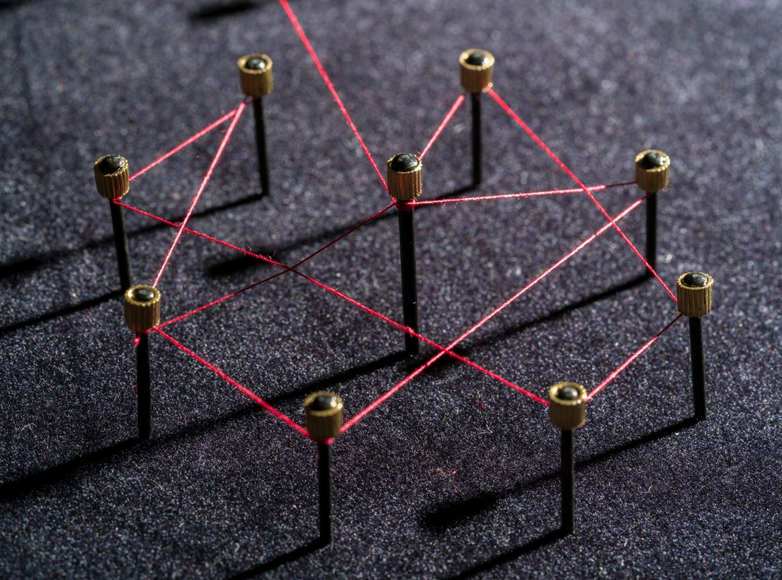 Nine pins connected be red string.