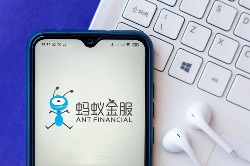 Mobile phone with Ant Financial app in front of keyboard and headphones