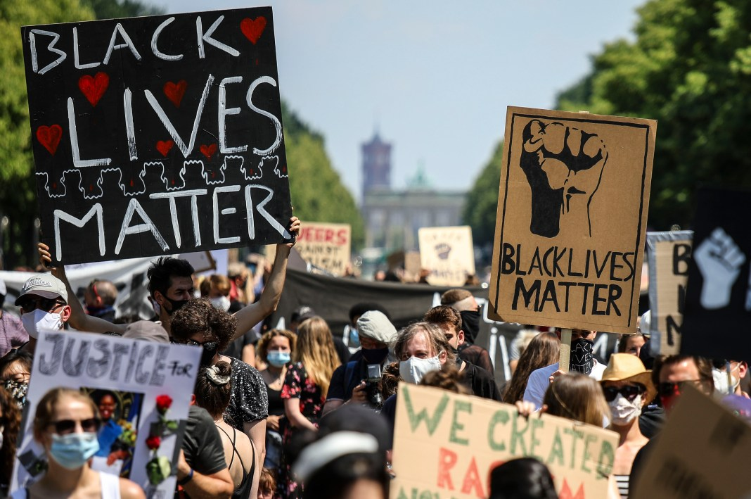 Protesers holding Black Lives Matter posters in Berlin.