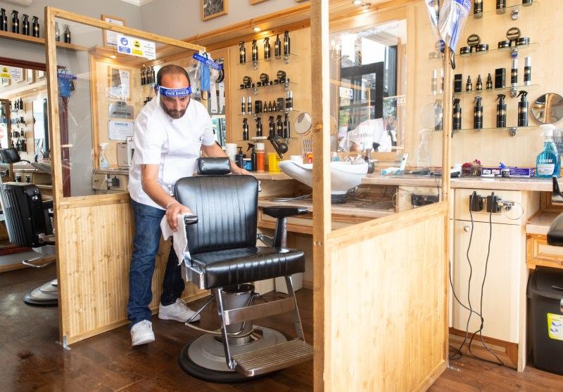 A hairdresser cleans the chair in a barber shop.
